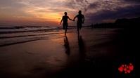 Couple running at beach evening time video Digitalanzeige (16:9) template
